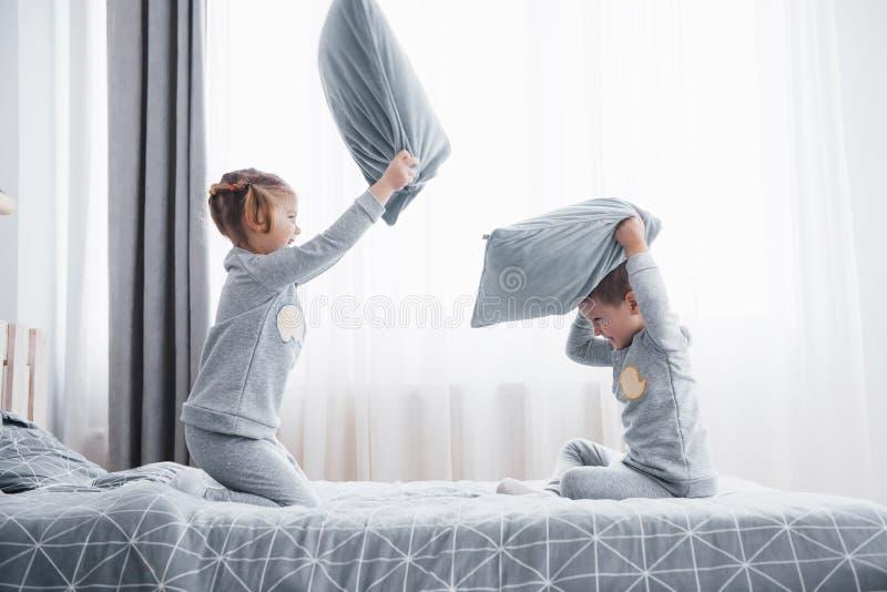 Le petit garçon et la fille ont présenté un combat d'oreiller sur le lit dans la chambre à coucher Battement vilain d'enfants ore images stock