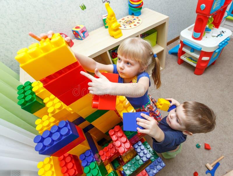 Le petit garçon et la fille très sérieux construisent la grande tour de bloc photographie stock libre de droits