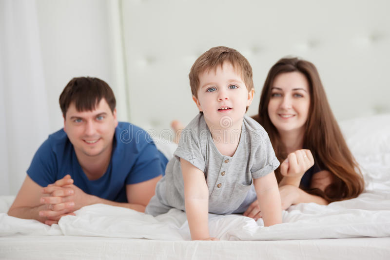 Le petit garçon et les parents sur des parents enfoncent les pyjamas de port photos libres de droits