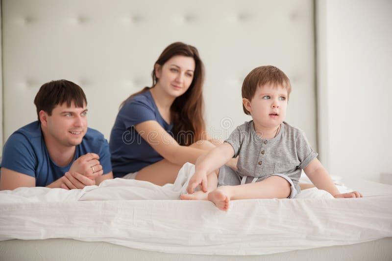 Le petit garçon et les parents sur des parents enfoncent les pyjamas de port images stock