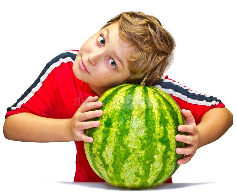 Le petit garçon examine la maturité de la pastèque photo libre de droits