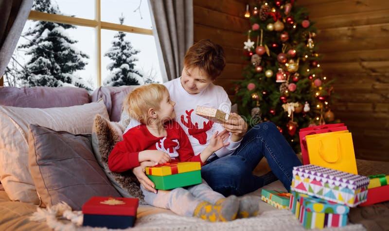 Le petit garçon excité et sa mère ou sa grand-mère sont assis sur leur lit près d'un arbre de Noël et ouvrent les cadeaux du Père photos stock