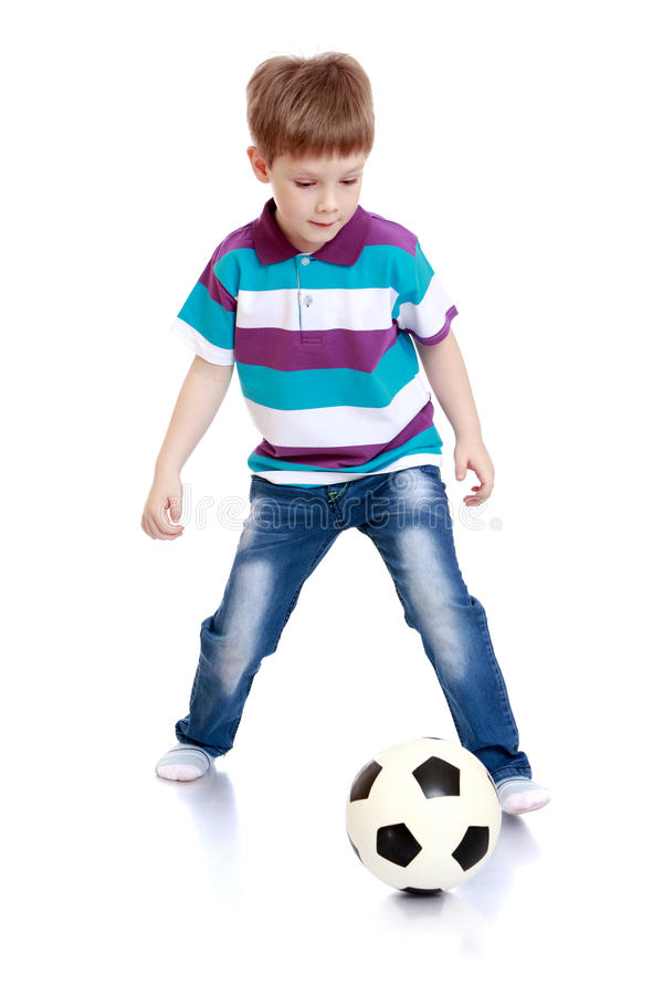 Le petit garçon gai jouant le football photographie stock