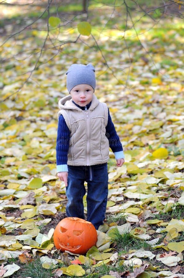 Le petit garçon heureux dans le chapeau et le gilet se tient avec le potiron de Halloween entouré par les feuilles tombées photo stock