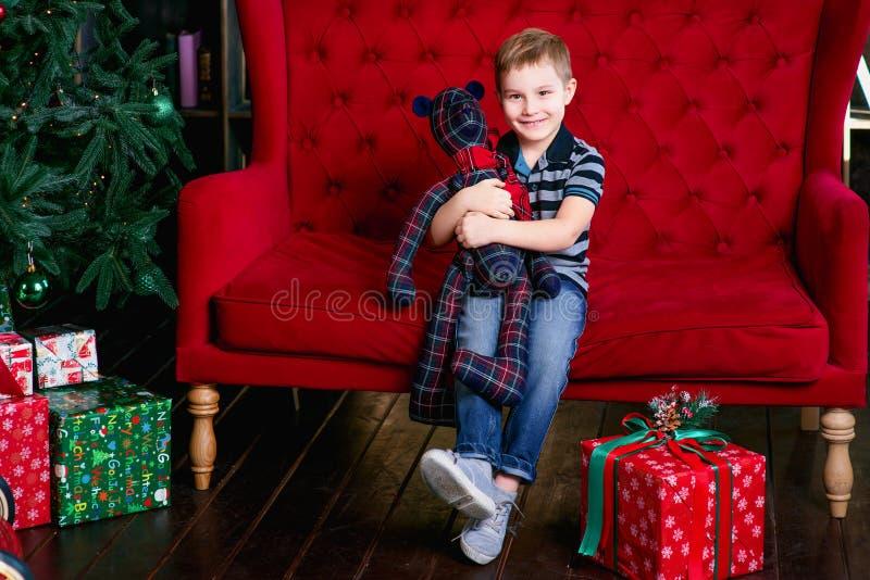 Le petit garçon heureux de sourire reposant et tenant le nounours concernent l'entraîneur rouge près de l'arbre de chrismas image libre de droits