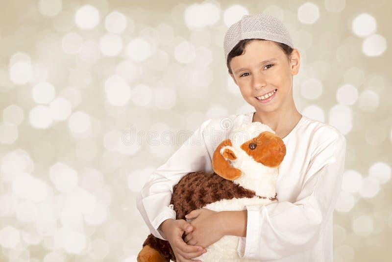 Le petit garçon heureux jouant avec ses moutons jouent - célébrer l'UL d'Eid photographie stock libre de droits