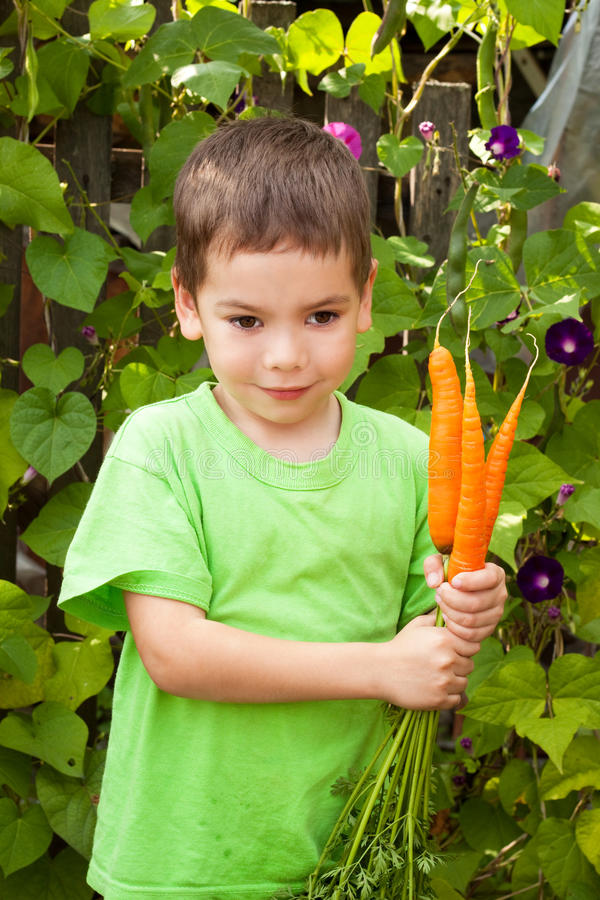 Le petit garçon heureux mange des raccords en caoutchouc dans un jardin photo stock