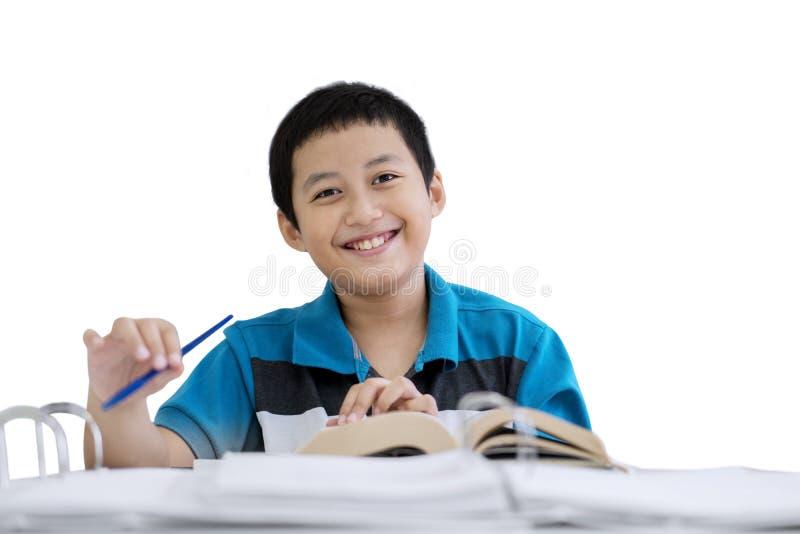 Le petit garçon heureux prend des notes sur le studio photographie stock