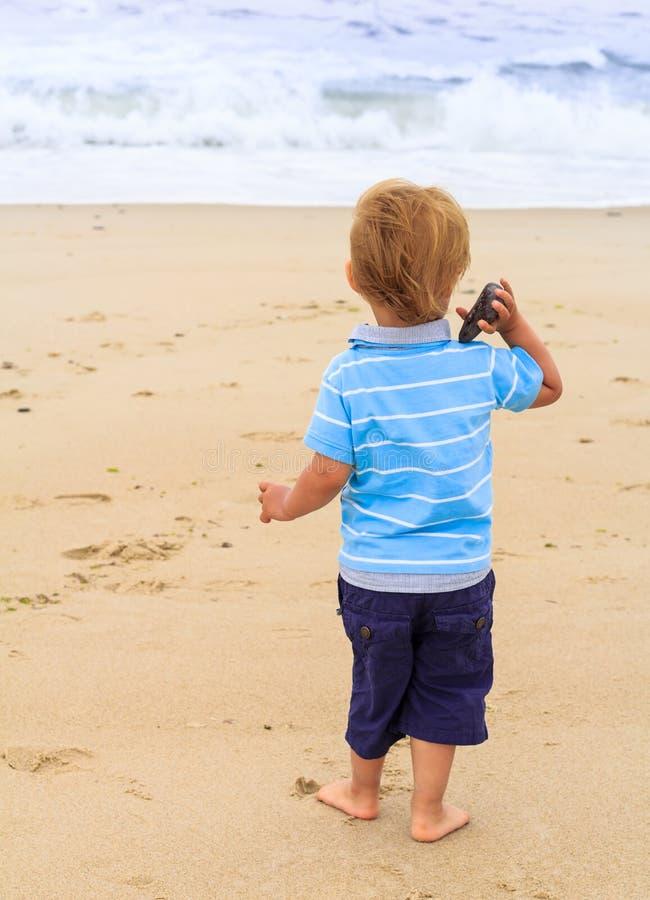 Le petit garçon jette une pierre dans la mer photographie stock libre de droits