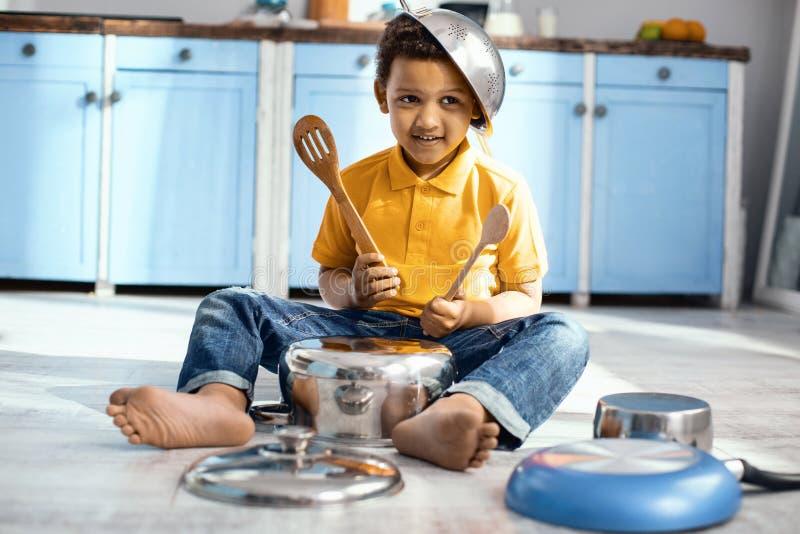Le petit garçon joyeux jouant sur la casserole aiment un batteur image stock