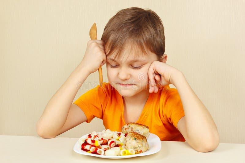 Le petit garçon mécontent ne veut pas manger des pâtes avec la rissole photographie stock libre de droits