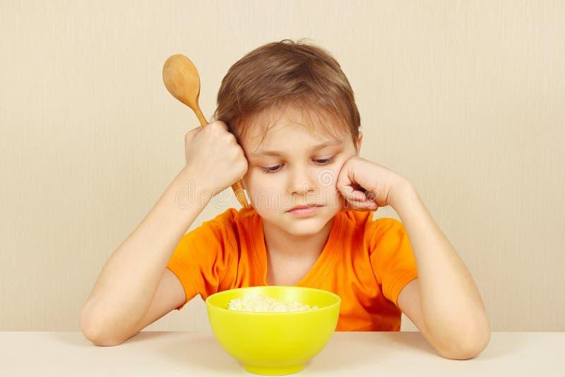 Le petit garçon malheureux ne veut pas manger de la céréale images stock