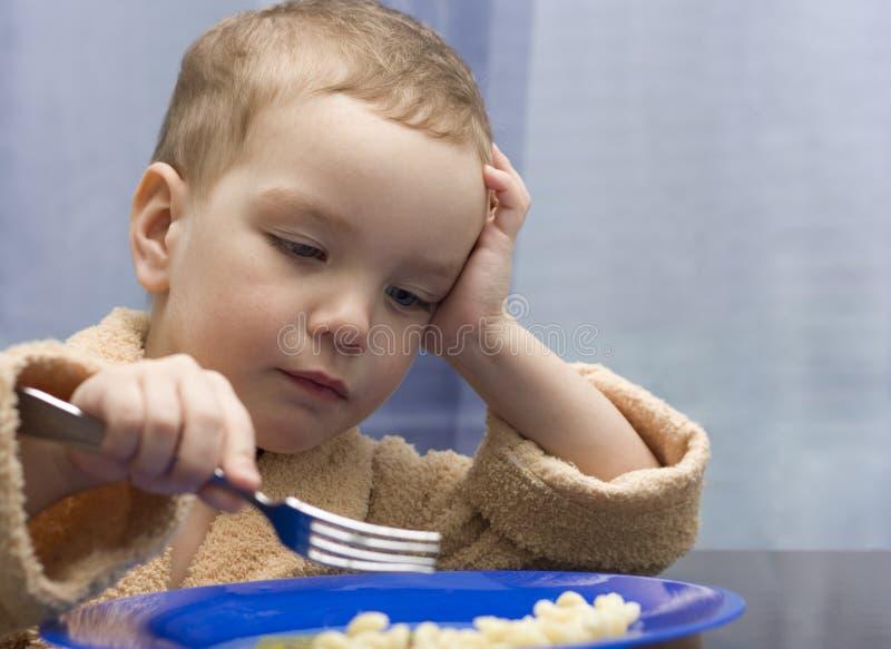 Le petit garçon mange. image libre de droits