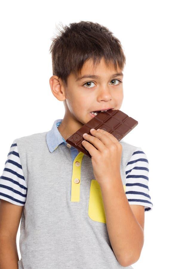 Le petit garçon mange du chocolat photos stock