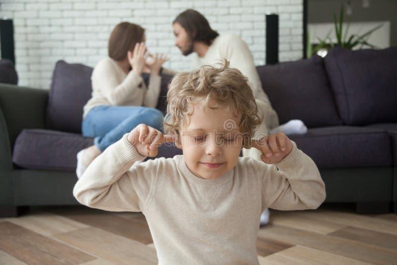 Le petit garçon met des doigts dans des oreilles, parents combattant au fond photos stock