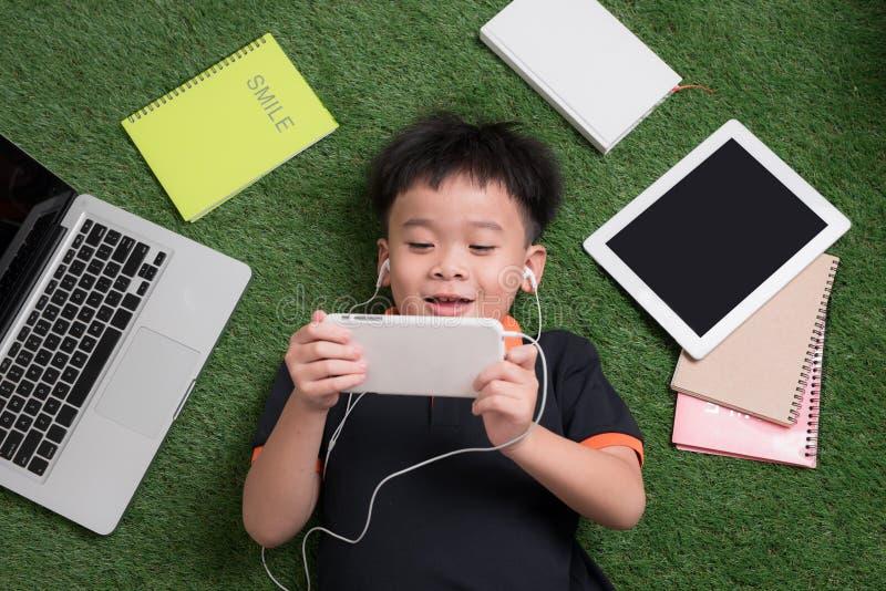 Le petit garçon mignon écoute la musique sur l'herbe avec son ordinateur portable, t image libre de droits