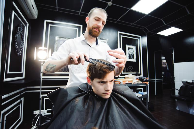 Le petit garçon mignon atteint la coupe de cheveux par le coiffeur le raseur-coiffeur photographie stock
