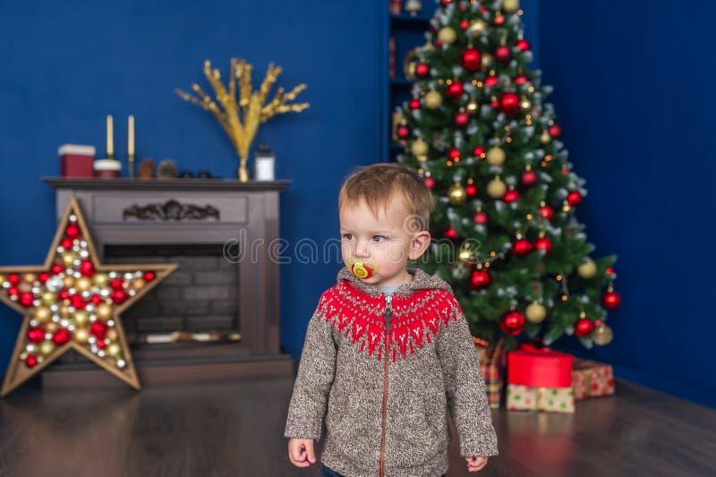 Le petit garçon mignon avec une tétine se tient près de l'arbre de Noël à la maison photographie stock libre de droits