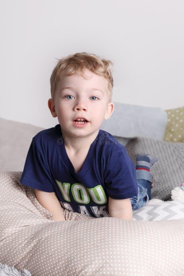 Le petit garçon mignon beau dans le T-shirt se trouve sur le lit photos libres de droits