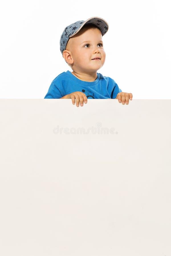 Le petit garçon mignon est au-dessus de l'affiche vide blanche recherchant photos stock