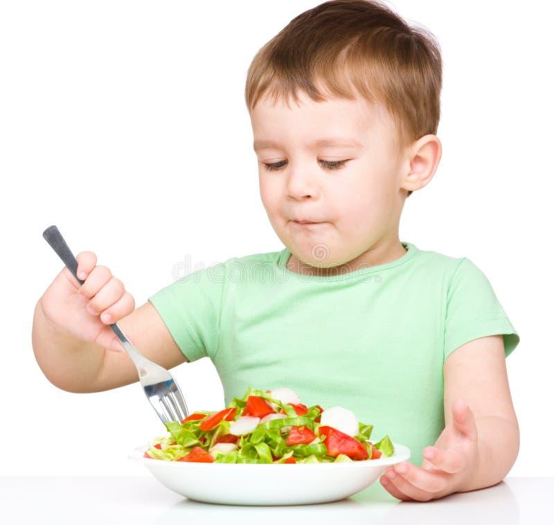 Le petit garçon mignon mange de la salade végétale photo stock