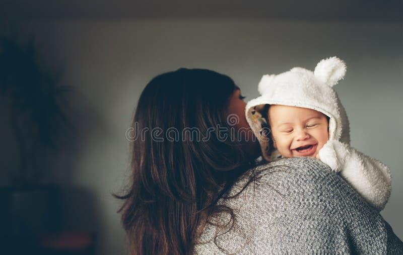 Le petit garçon mignon souriant dans son ` s de mère arme images libres de droits