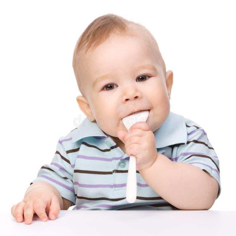 Le petit garçon mord une cuillère se reposant à la table images libres de droits