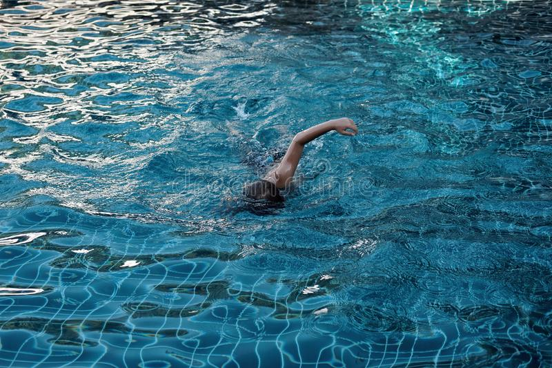 Le petit garçon nage dans la piscine photos libres de droits
