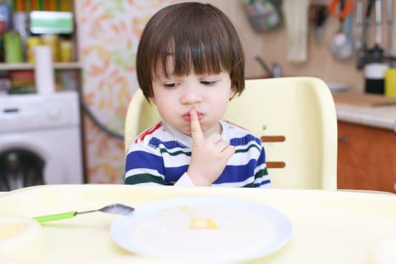Le petit garçon ne veulent pas manger du gruau photo libre de droits