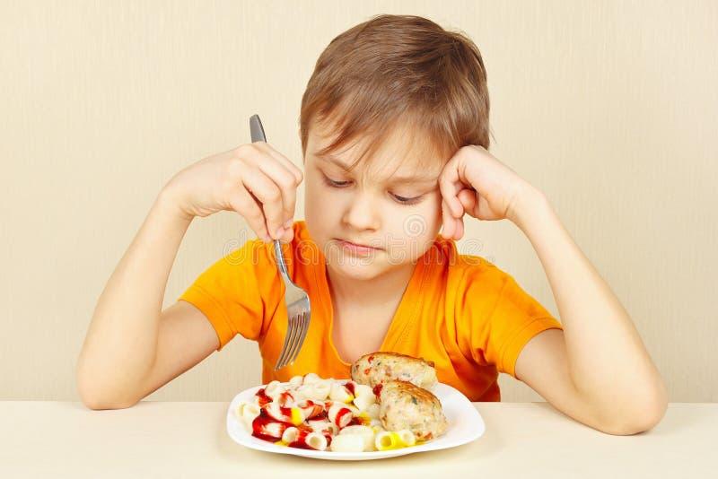 Le petit garçon ne veut pas manger des pâtes avec la côtelette image libre de droits