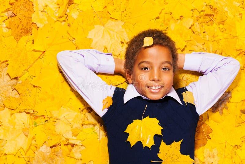 Le petit garçon noir heureux dans l'érable d'automne part images libres de droits