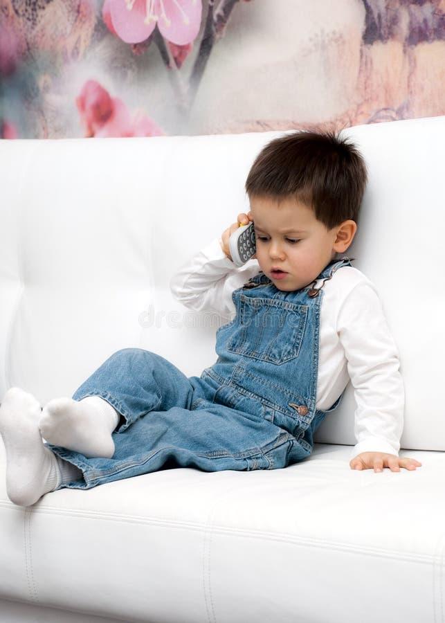 Le petit garçon parle au téléphone portable photographie stock libre de droits