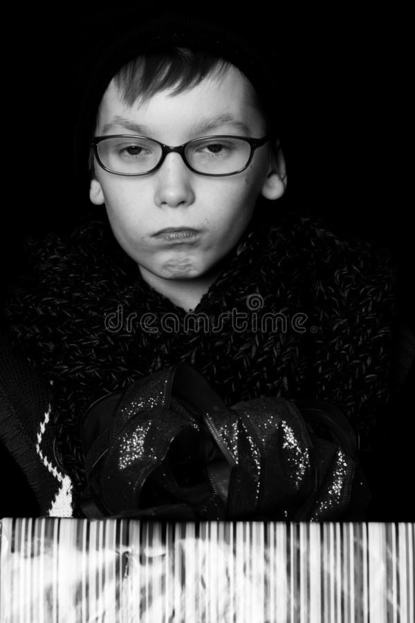 Le petit garçon sérieux ou l'enfant mignon de ballot dans les verres, le chapeau et l'écharpe tricotée à la mode sur le fond noir photo stock
