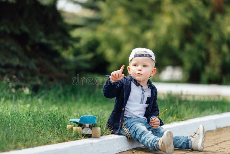 Le petit garçon s'asseyent au fond de vert de tache floue photo libre de droits