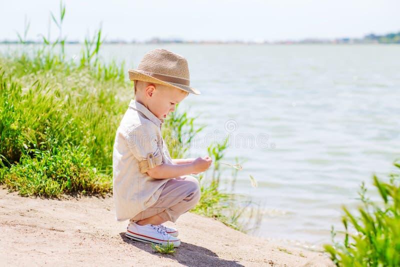 Le petit garçon s'assied sur le lac et jouer photos libres de droits