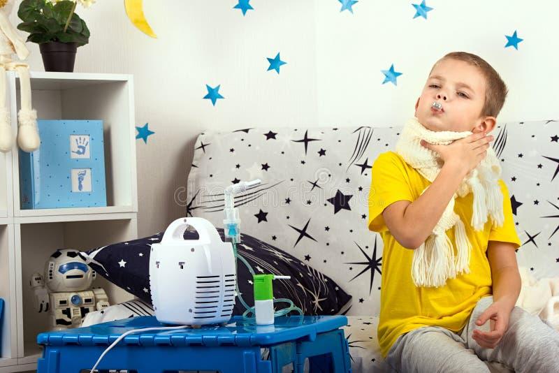 Le petit garçon sent la douleur dans la gorge, mesure la température images stock