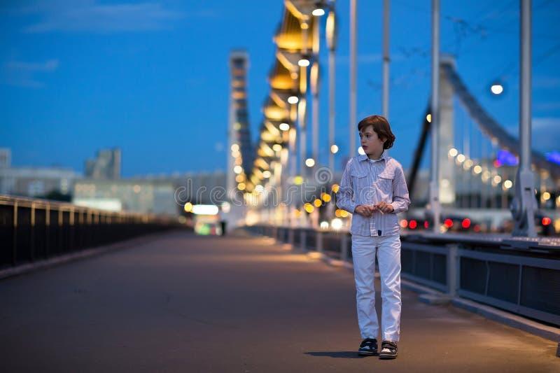Le petit garçon seul marchant a effrayé sur le pont dans l'obscurité images libres de droits