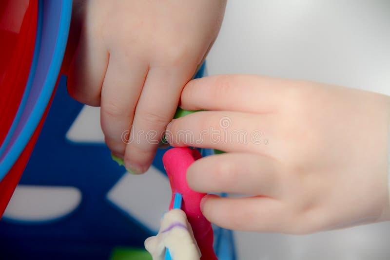 Le petit garçon trois années s'assied sur la table et joue avec de la pâte à modeler et les jouets, les cubes et les matrices en  image libre de droits