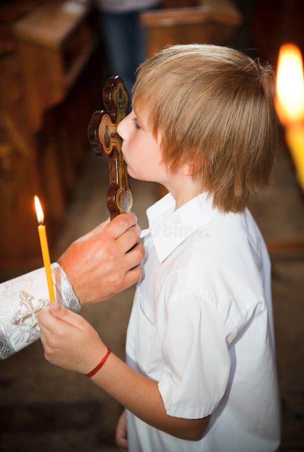 Le petit garçon une croix de baiser images stock