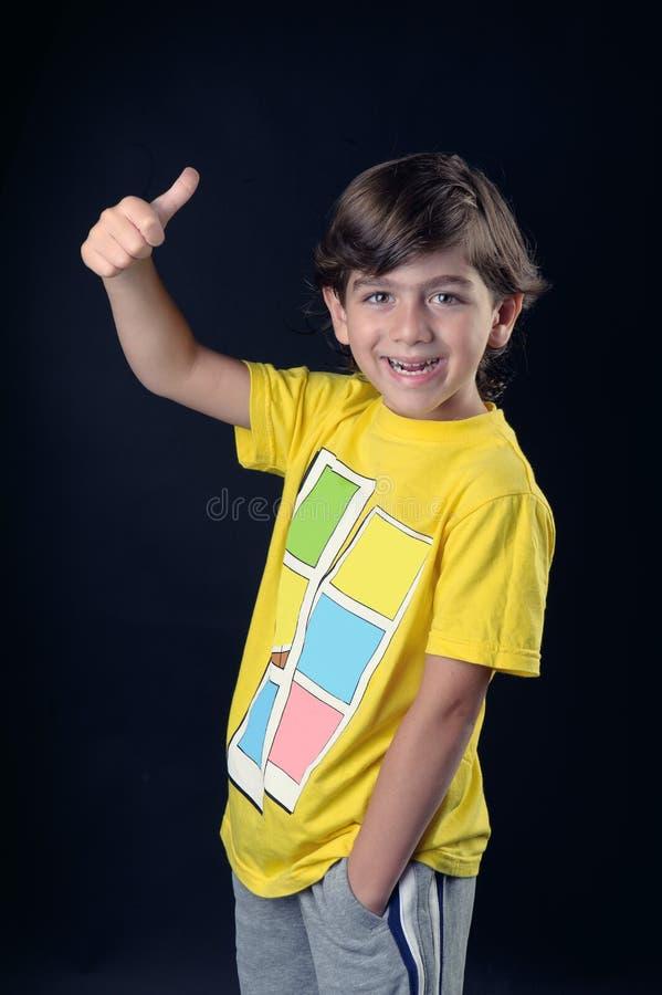 Le petit gosse de sourire avec des pouces lèvent le signe image libre de droits