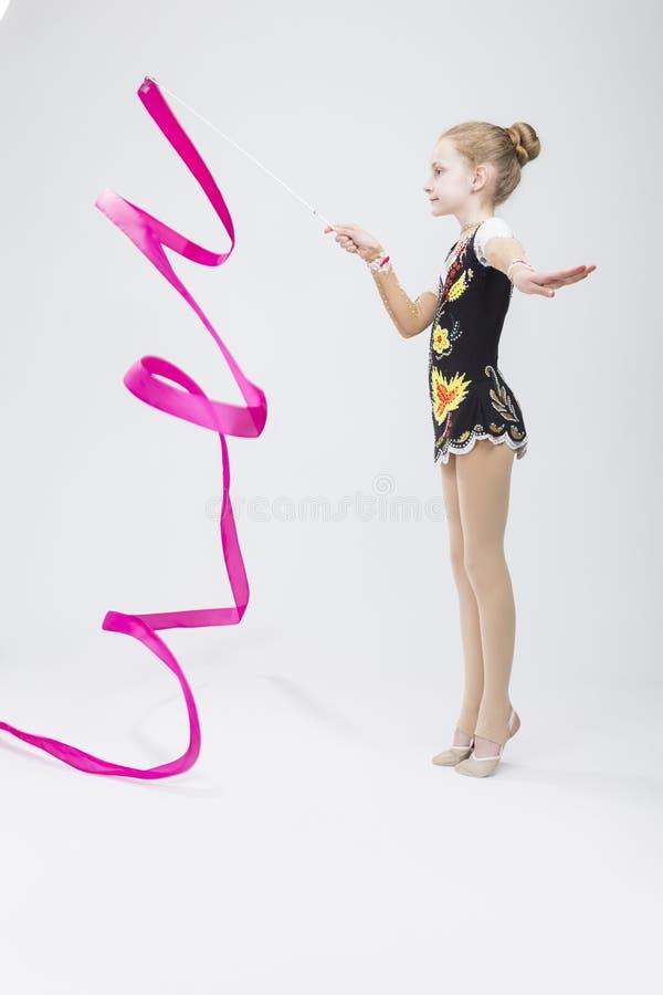Le petit gymnaste rythmique féminin caucasien dans le costume concurrentiel professionnel faisant le ruban artistique se développ photos stock
