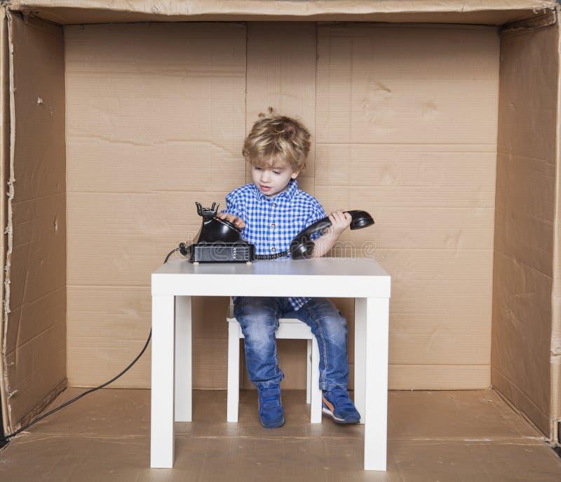 Le petit homme d'affaires compose le numéro au téléphone images libres de droits