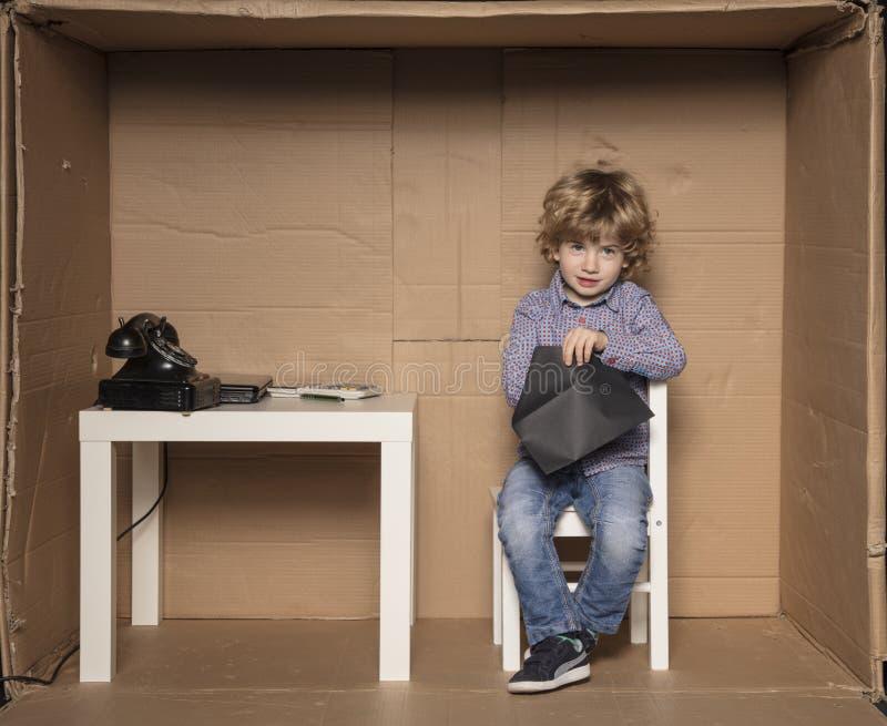 Le petit homme d'affaires vérifie le contenu d'une enveloppe photographie stock libre de droits