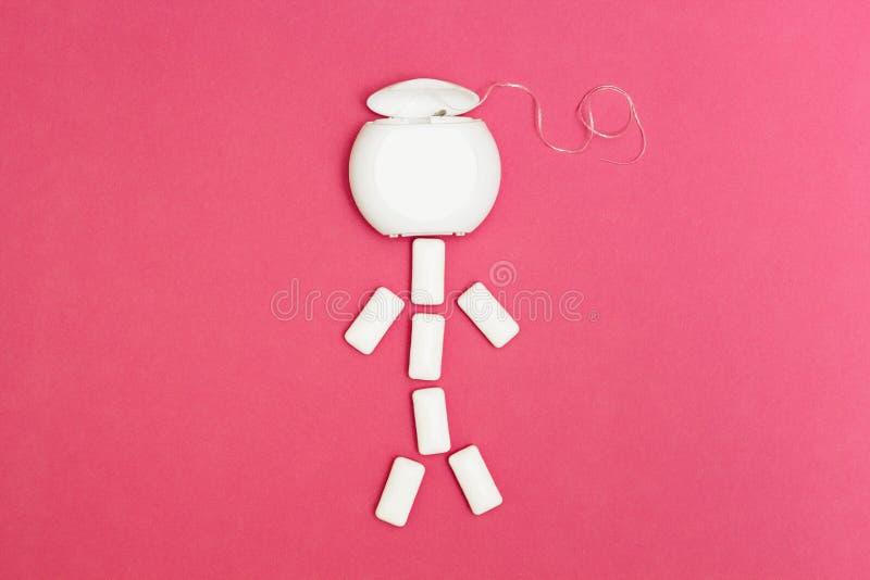 Le petit homme du chewing-gum et fil dentaire sur un fond rose, l'espace pour le texte images libres de droits
