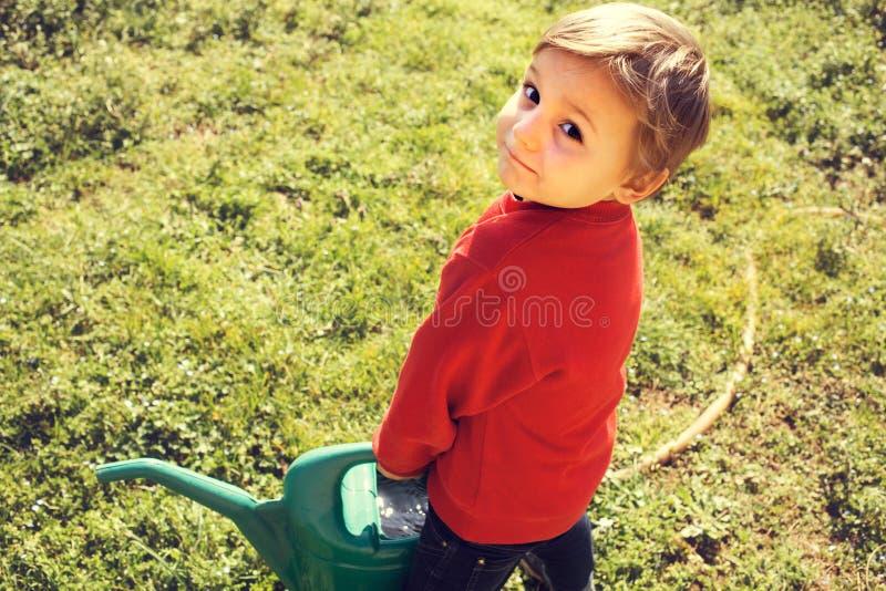 Le petit jardinier portent l'arroser-pot lourd photo stock