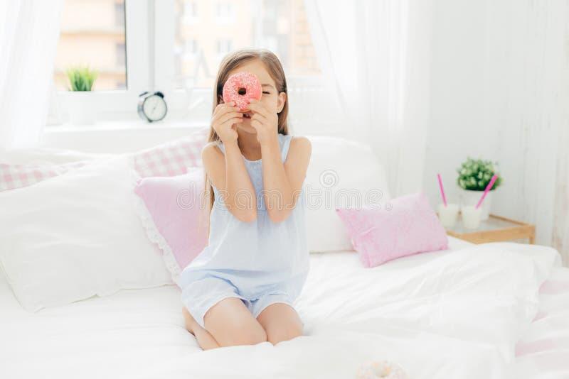 Le petit joli enfant féminin tient le beignet doux savoureux, pose dans la chambre à coucher sur le lit comfortabled, habillé dan photo stock