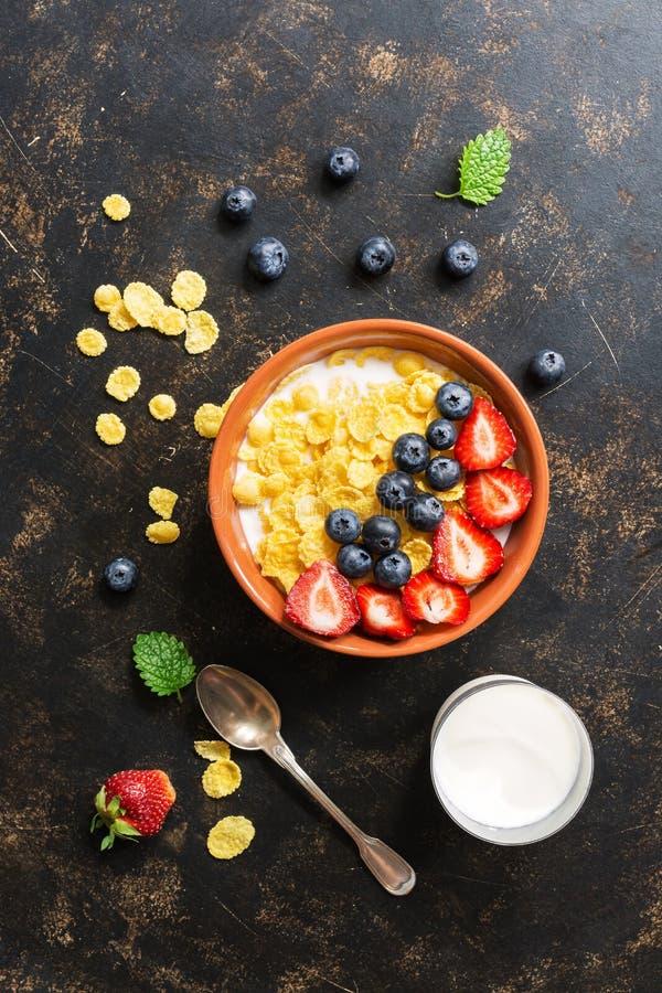Le petit-maïs frais s'écaille avec du lait, des fraises et des myrtilles sur un fond foncé Vue d'en haut, configuration plate photos libres de droits