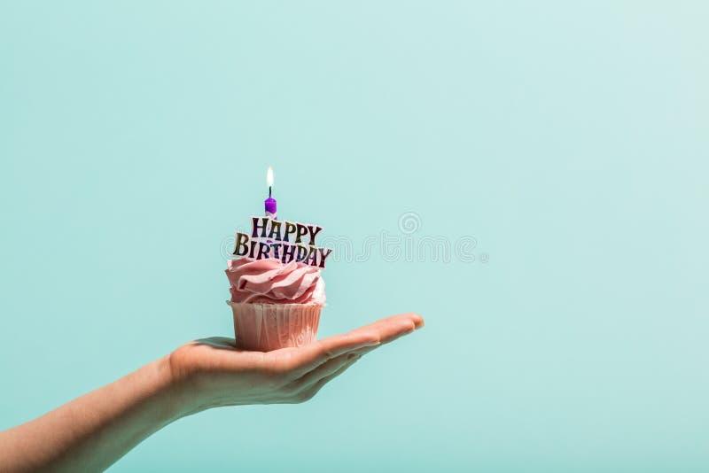 Le petit pain d'anniversaire avec la bougie s'est tenu chez la main du ` s de la femme photos stock