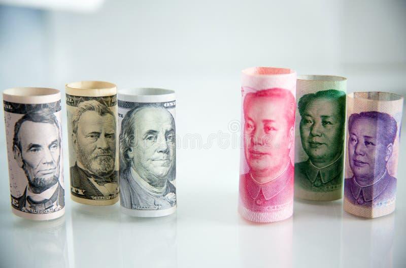 le petit pain de billet de banque, le petit pain du dollar et les yuans roulent concept de concurrence d'échecs d'économie petit  photographie stock