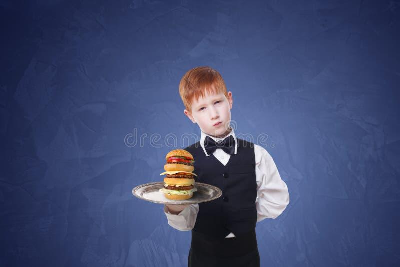 Le petit serveur triste de garçon se tient avec l'hamburger de portion de plateau images libres de droits